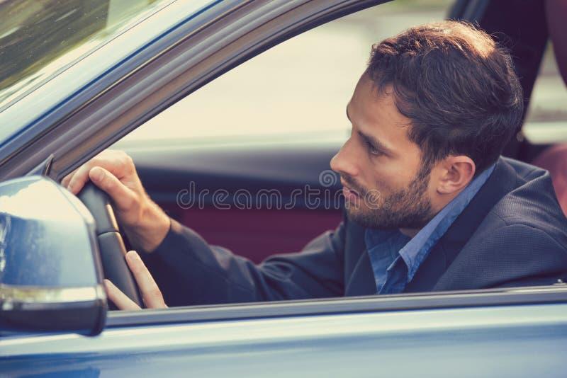 驾驶他的汽车的侧面窗视图困被疲劳的被用尽的人 免版税库存照片