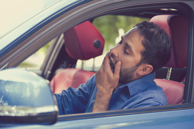 驾驶他的汽车的困被疲劳的打呵欠的被用尽的年轻人 免版税库存图片