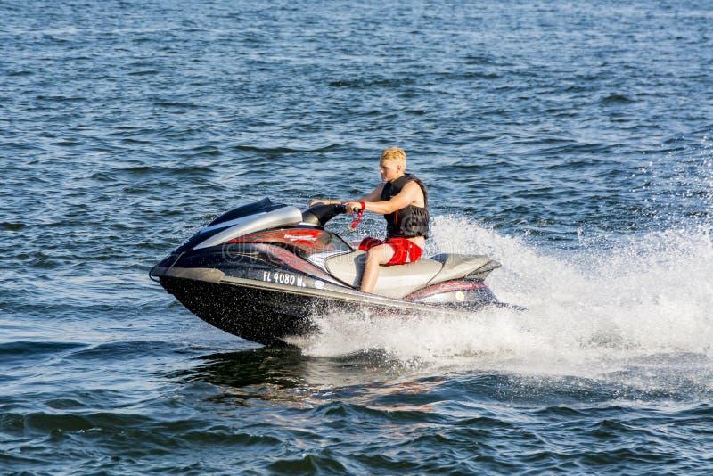 驾驶水滑行车的年轻人 免版税库存照片