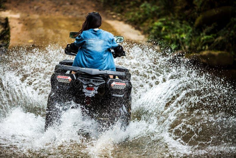 驾驶ATV的女孩通过河狂欢 库存图片