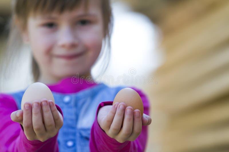 骄傲地举行和显示对照相机两大干净的鸡蛋的逗人喜爱的滑稽的小微笑的愉快的白肤金发的女孩被弄脏的画象室外 免版税库存照片