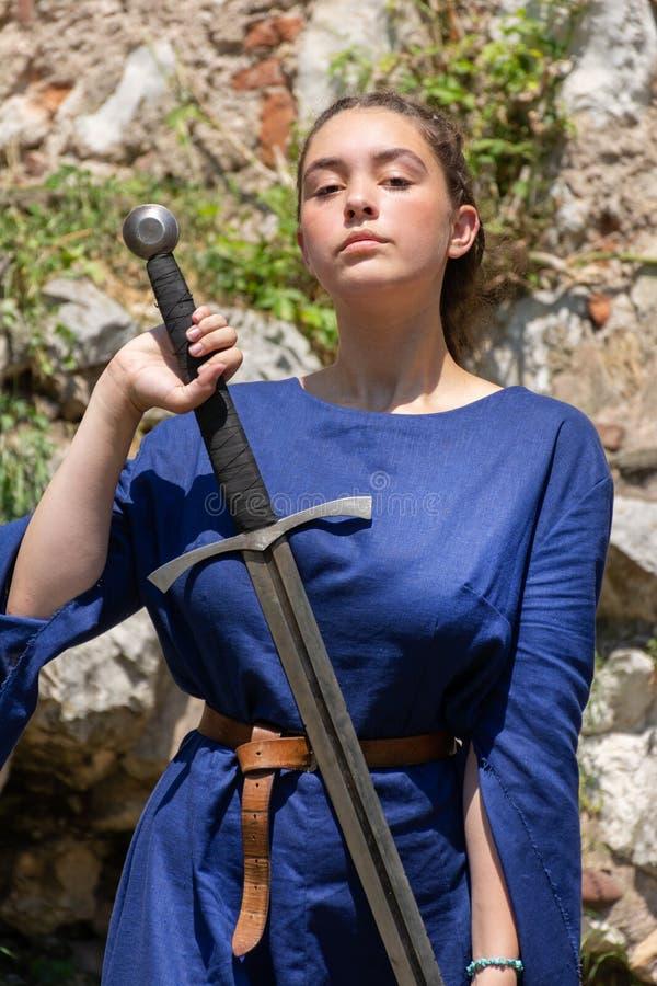 骄傲地在手中拿着一把大剑的一件蓝色礼服的中世纪夫人 免版税库存照片
