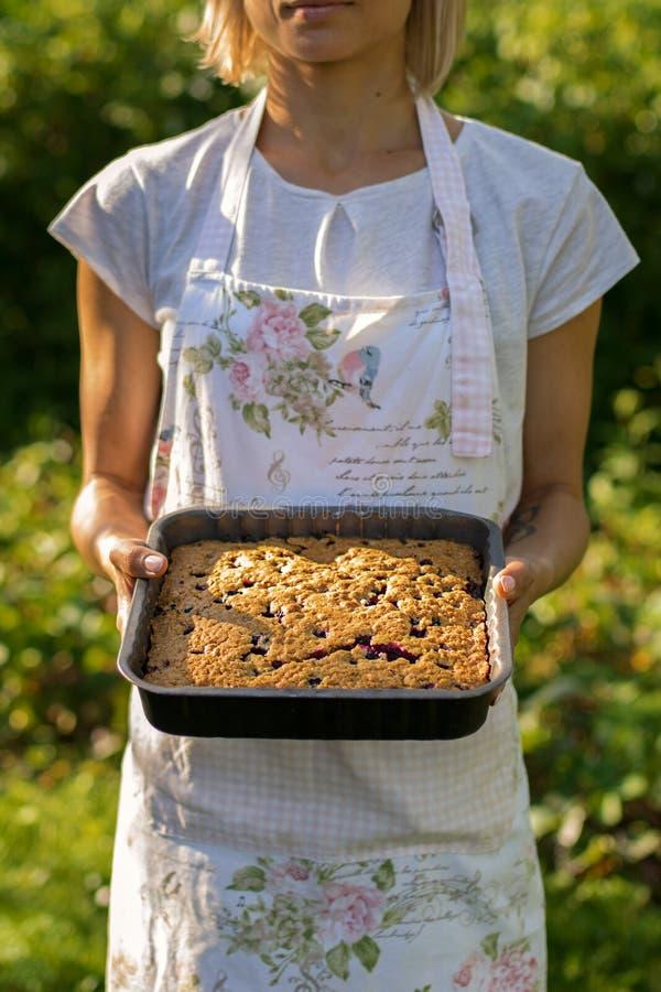 骄傲地拿着新近地被烘烤的蓝草莓饼的一位年轻主妇 免版税库存图片