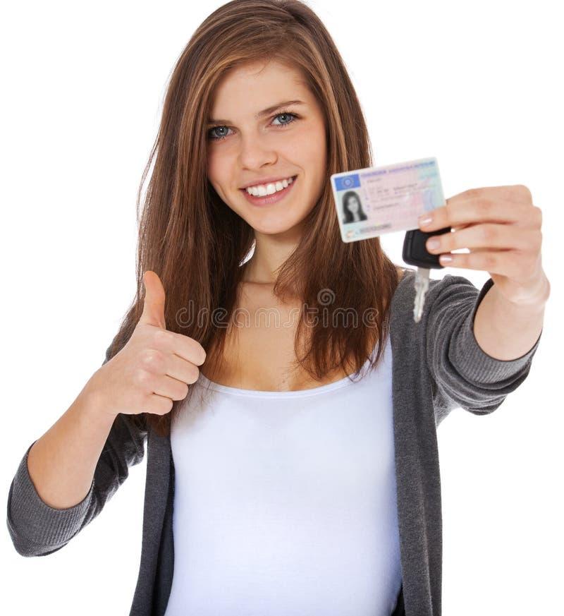 骄傲地显示她的驾驶执照的十几岁的女孩 库存图片