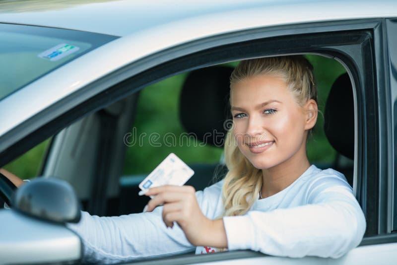 骄傲地显示她的驾驶执照的年轻女人 免版税库存照片