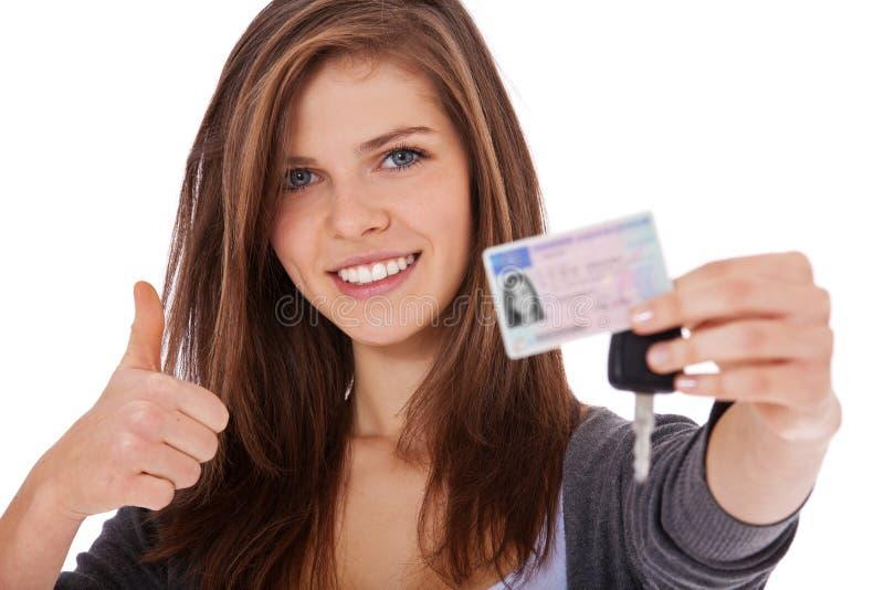 骄傲地显示驾驶执照的十几岁的女孩 库存图片