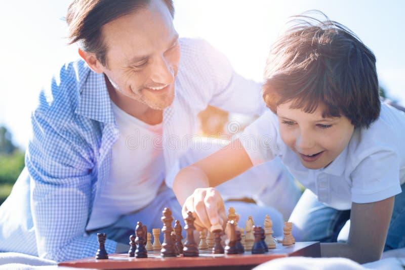 骄傲的下棋的父亲观看的儿子 图库摄影