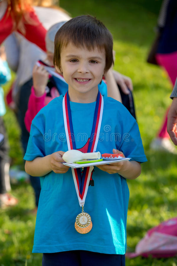 骄傲的学龄前男孩,拿着奖和奖牌 库存照片