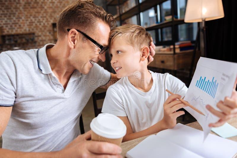 骄傲的拿着与图的父亲拥抱的儿子打印输出 库存图片