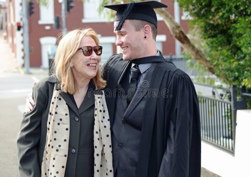 骄傲的母亲和拥抱大学毕业生的儿子微笑& 免版税图库摄影