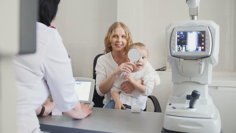 验光师在眼科医生屋子里检查儿童` s眼力-母亲和孩子 库存照片
