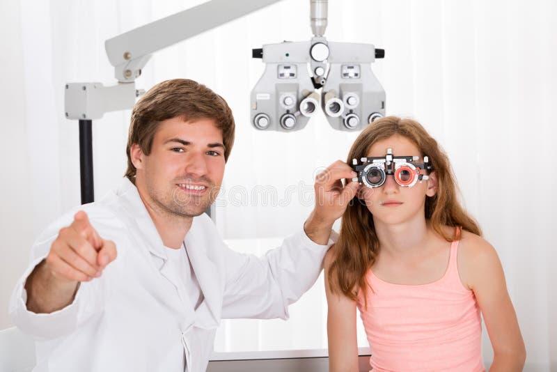 验光师检查的女孩与Phoropter的` s视觉 库存照片