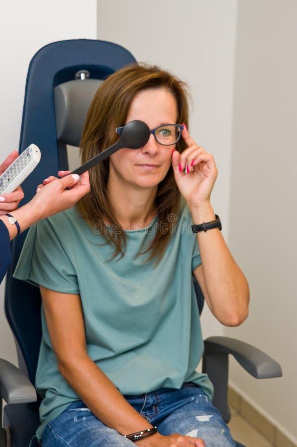 验光师沙龙的妇女检查她的眼力的 库存图片