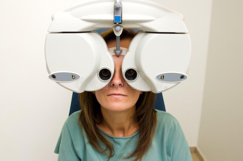 验光师沙龙的妇女检查她的眼力的 免版税库存图片