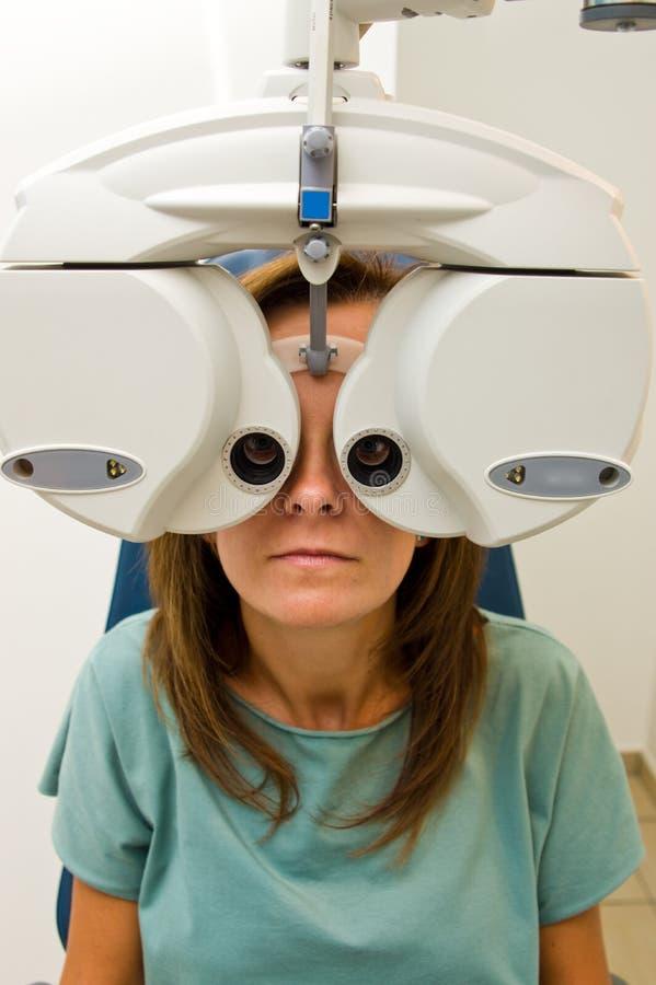 验光师沙龙的妇女检查她的眼力的 库存照片