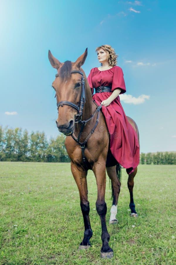 骑一匹棕色马的一件长的红色礼服的美丽的女孩 免版税库存图片