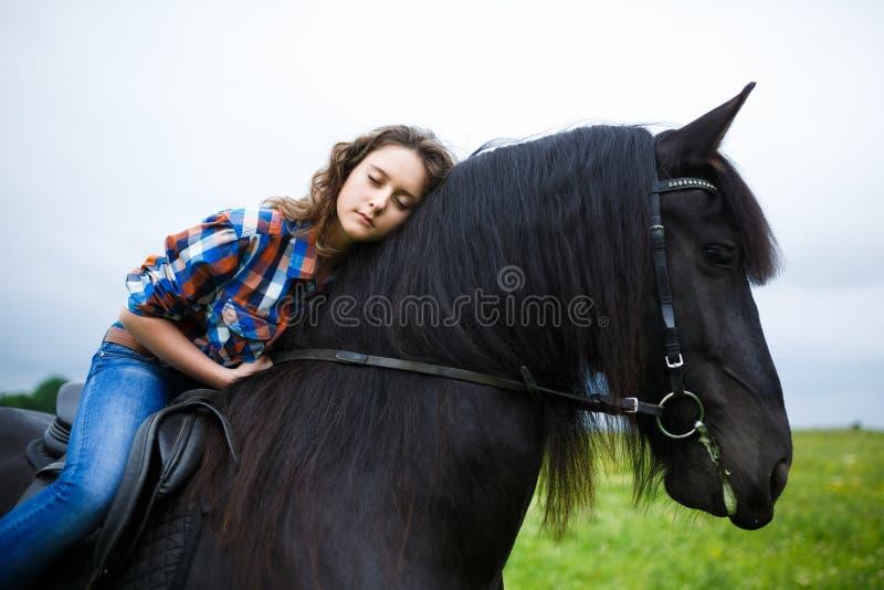 骑一匹马的美丽的女孩在乡下 图库摄影