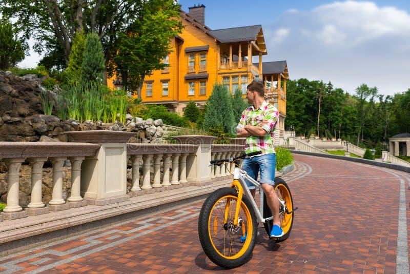 骑一辆五颜六色的黄色自行车的年轻人 图库摄影