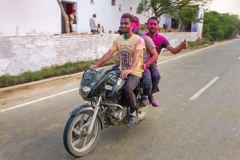 骑一辆自行车的三个未认出的印地安人盖用搽粉的染料在Holi节日的期间在印度 免版税库存照片
