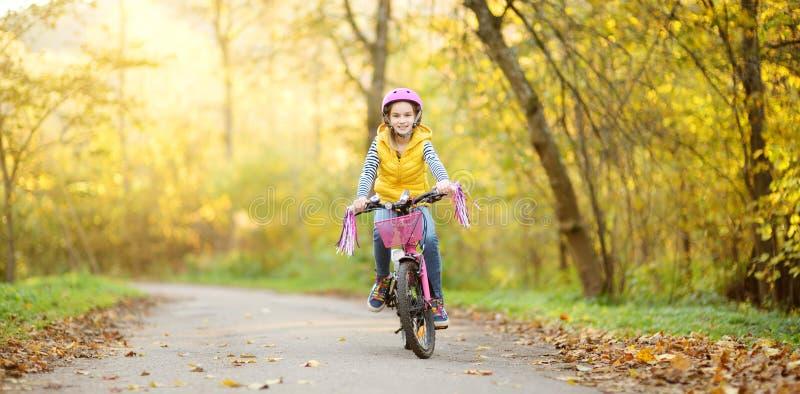 骑一辆自行车的可爱的少女在城市公园在晴朗的秋天天 r 免版税库存图片