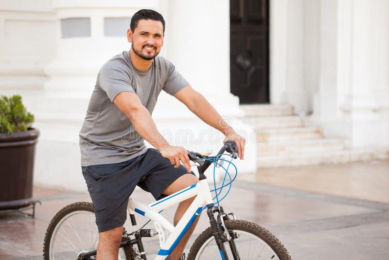 骑一辆自行车的可爱的拉丁人在城市 库存图片