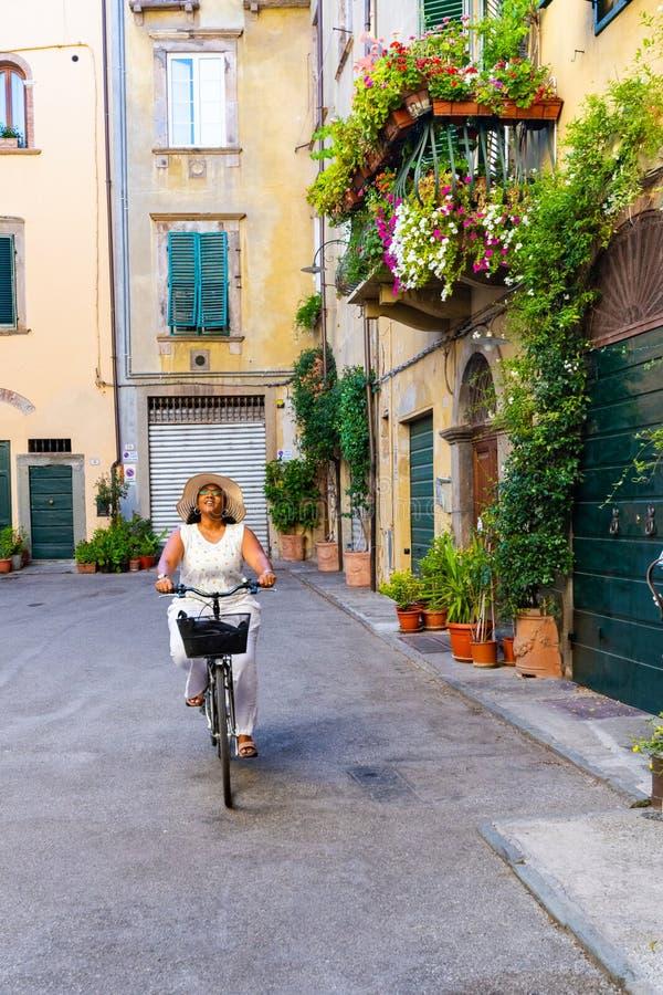 骑一辆自行车的妇女在意大利 图库摄影