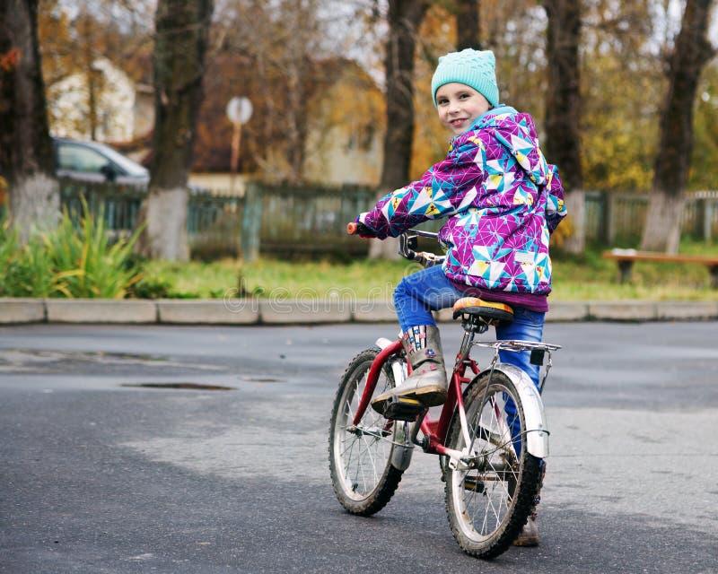 骑一辆自行车的小女孩在秋天公园 免版税库存照片