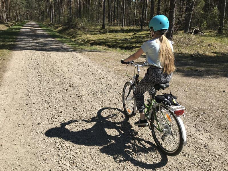 骑一辆自行车的少女在波兰乡下 库存图片