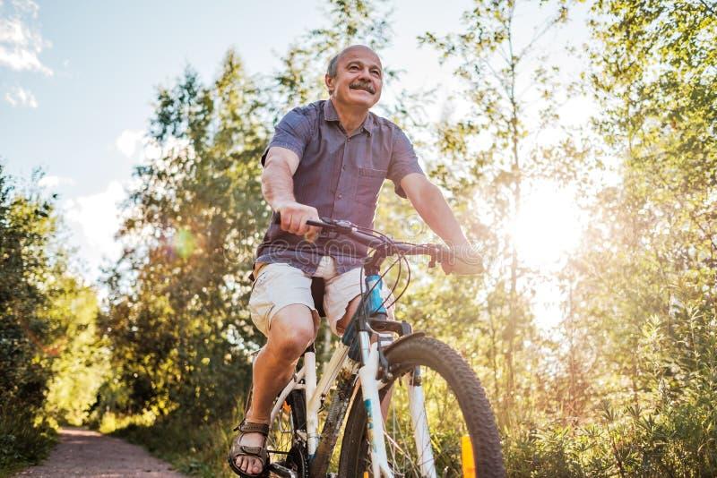 骑一辆自行车的快乐的老人在公园在一个美好的晴天 免版税库存照片