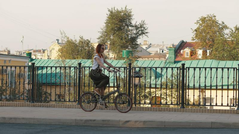 骑一辆自行车的红发妇女在城市在背景大厦和屋顶房子 图库摄影