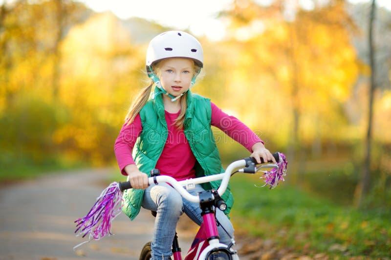 骑一辆自行车的逗人喜爱的女孩在城市公园在晴朗的秋天天 r 免版税库存图片