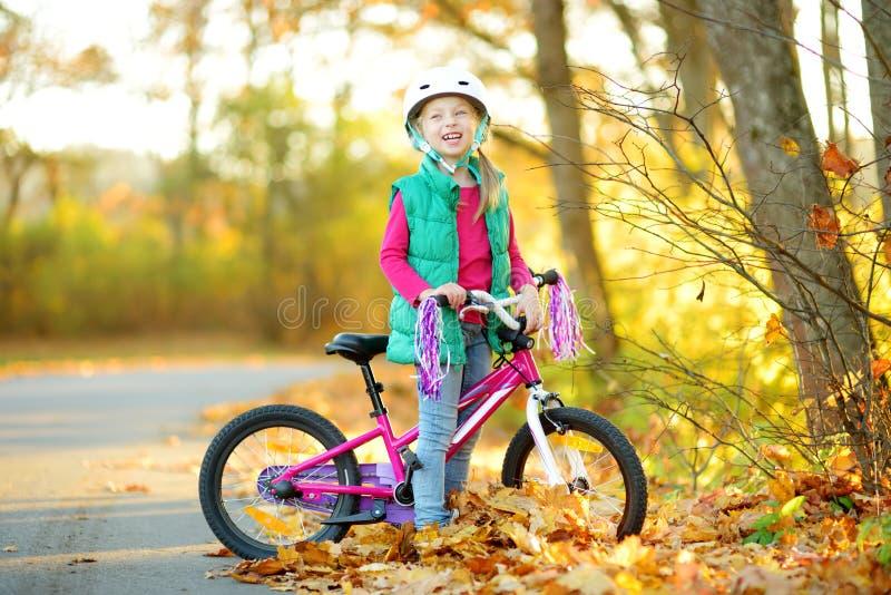 骑一辆自行车的逗人喜爱的女孩在城市公园在晴朗的秋天天 r 图库摄影