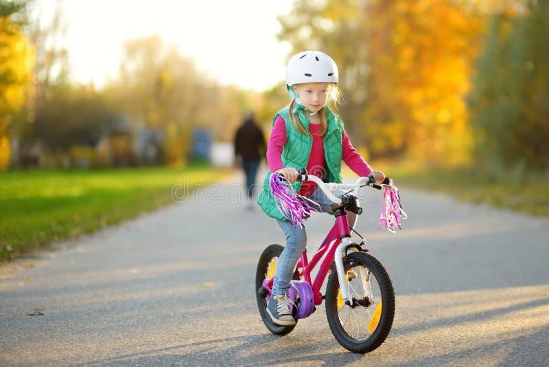 骑一辆自行车的逗人喜爱的女孩在城市公园在晴朗的秋天天 r 库存图片