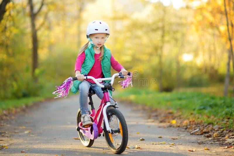 骑一辆自行车的逗人喜爱的女孩在城市公园在晴朗的秋天天 r 免版税图库摄影