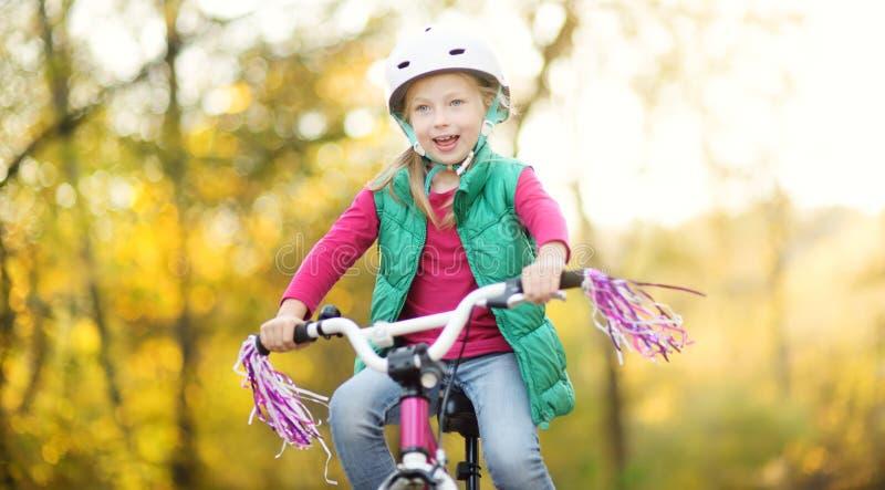 骑一辆自行车的逗人喜爱的女孩在城市公园在晴朗的秋天天 r 库存照片