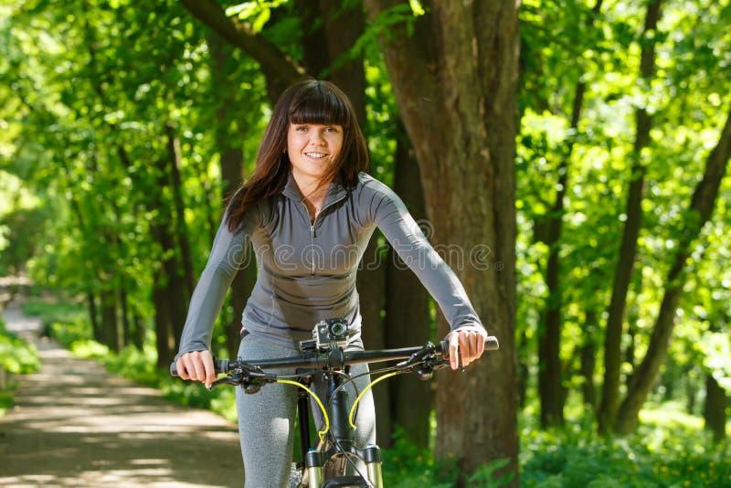 骑一辆自行车的骑自行车者妇女在公园 库存照片