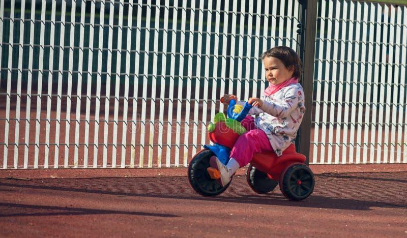 骑一辆3轮子自行车的逗人喜爱的三岁的小孩在操场 免版税库存图片