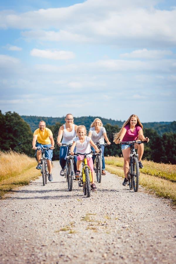 骑他们的自行车的家庭在下午在乡下 图库摄影
