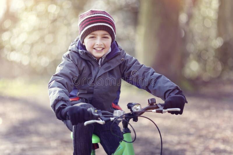 骑他的自行车和笑在秋叶的男孩在公园 免版税库存照片