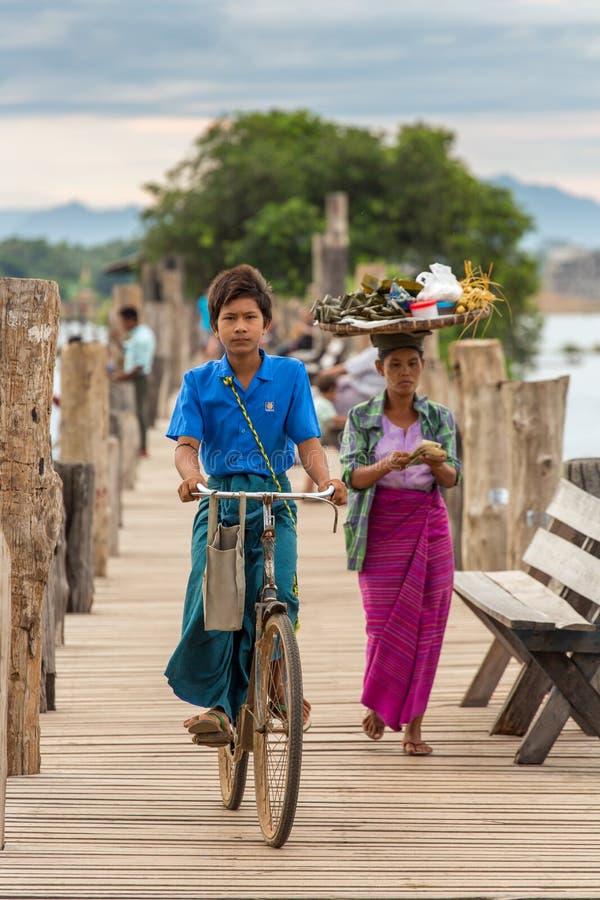 骑他的自行车的缅甸男孩在著名U-Bein桥梁在Amarapura在曼德勒,缅甸附近 免版税库存图片