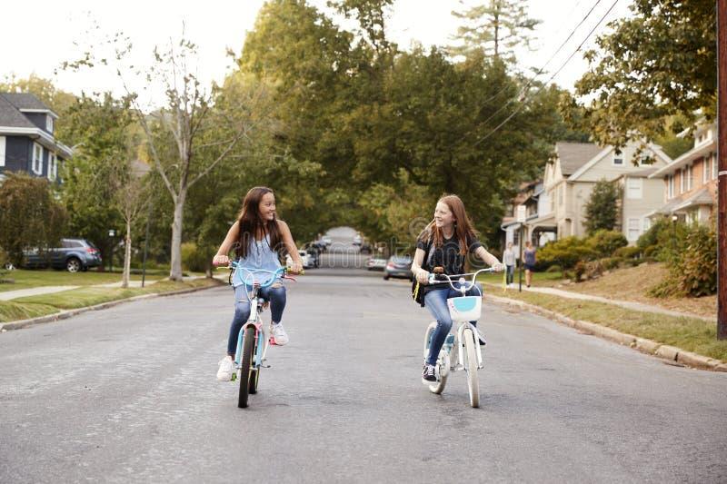 骑在一条静街,正面图的两个青少年的女孩自行车 免版税库存照片