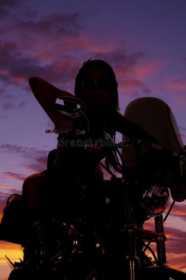 骑在日落的妇女的剪影一辆摩托车 库存照片