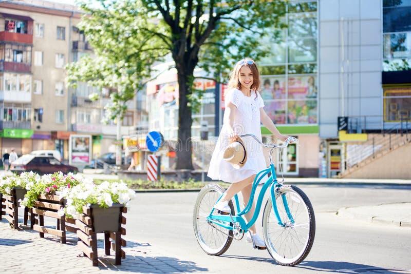 骑在现代城市大厦前面的白色礼服的微笑的年轻女性蓝色自行车在夏日 免版税库存照片