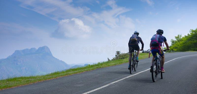 骑在路的两个山骑自行车的人自行车 免版税库存图片