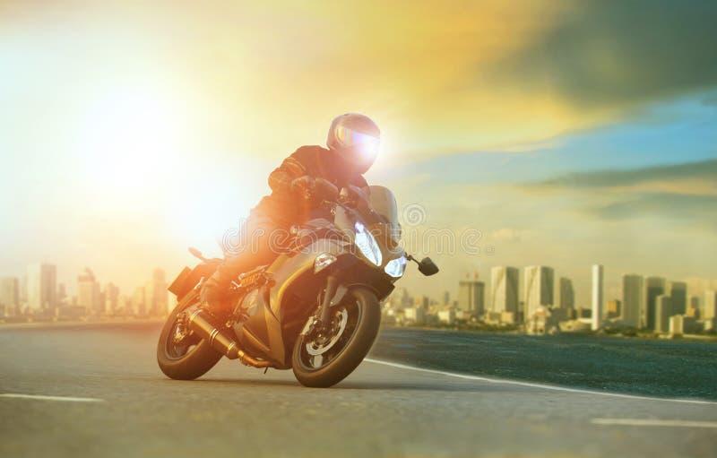 骑大摩托车的年轻人倾斜在与urba的锋利的曲线 免版税库存照片