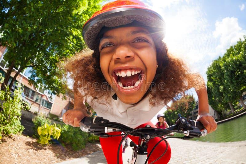 骑她的自行车的愉快的非洲女孩晴天 免版税库存图片