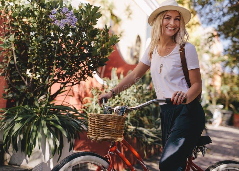 骑她的自行车的美丽的妇女在城市 库存照片