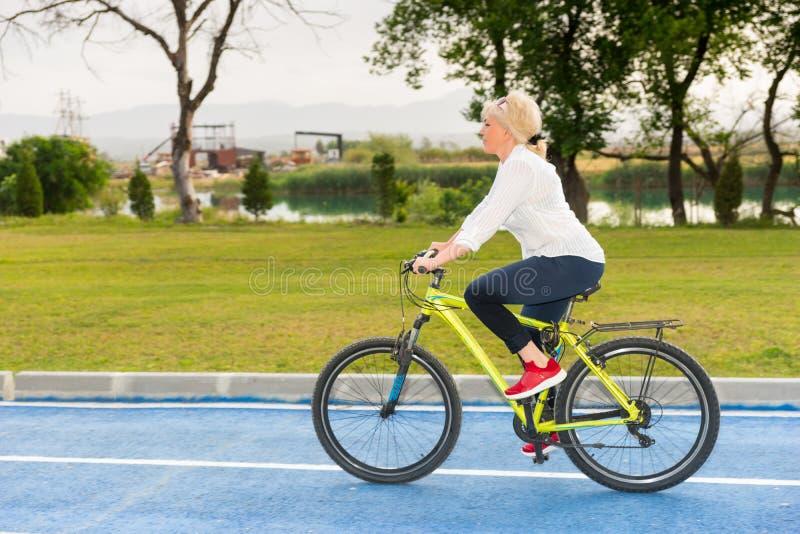 骑她的通过湖或河的白肤金发的妇女自行车 免版税库存图片