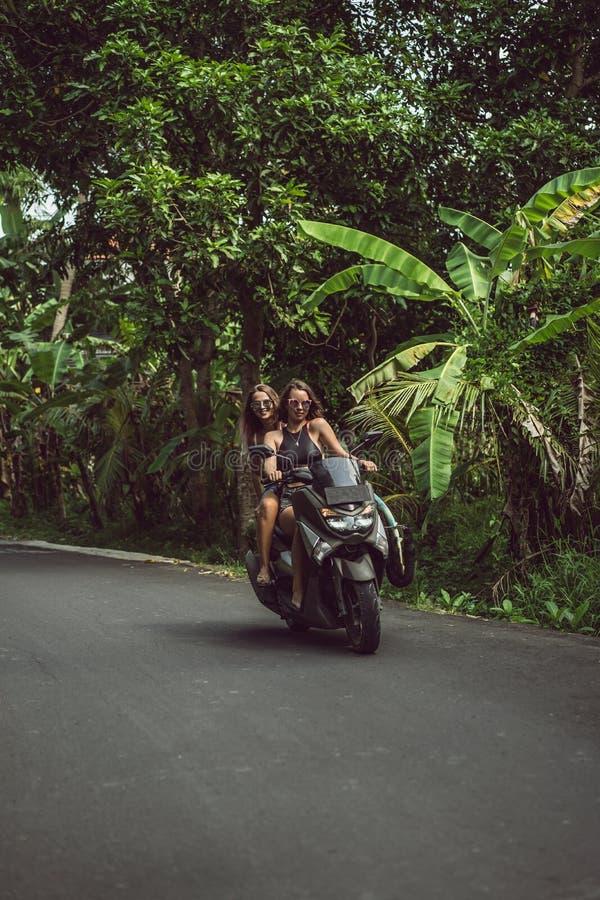骑摩托车的可爱的年轻女人在路 免版税库存图片