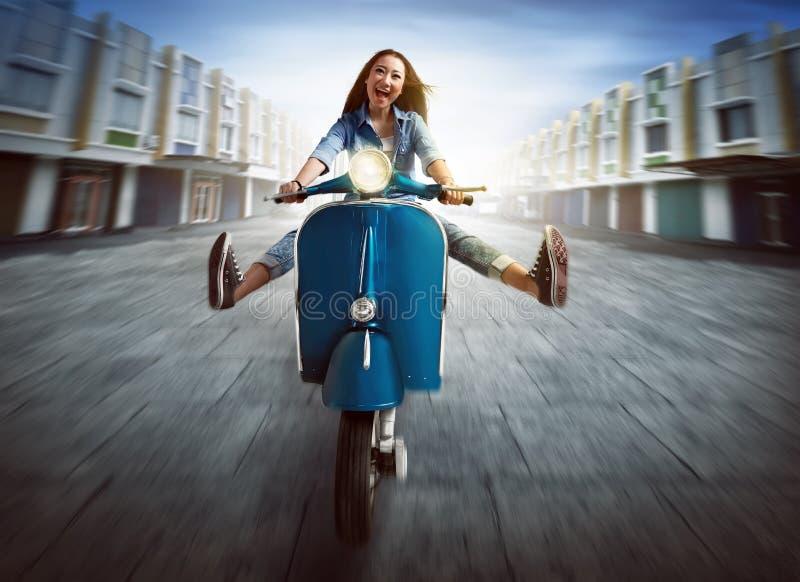 骑摩托车的美丽的年轻亚裔妇女 免版税库存图片